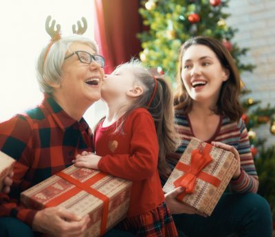 Merry Christmas and Happy Holidays! Grandma, grandpa, mum and child exchanging gifts. Parents and daughters having fun near tree indoors. Loving family with presents in room.