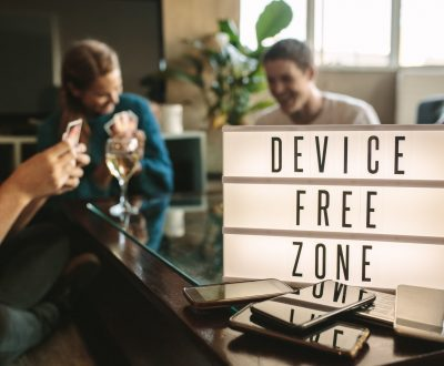 Mobile phones on table with device free zone sign. Group of young men and woman hanging out together at no phone zone.